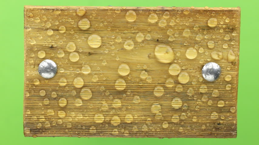 perçin : Wind blows off water drops, with wooden board with iron screws, isolated on green.