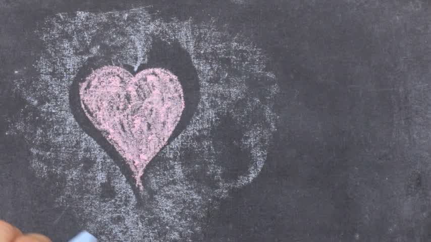 tablica : Heart painted with pink chalk, on a dark background, chalkboard. Boy draws heart. Valentines day card.