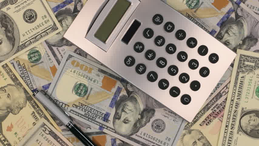 earnings : Rotation of the pen and calculator lying on the dollars. Top view. Stock Footage