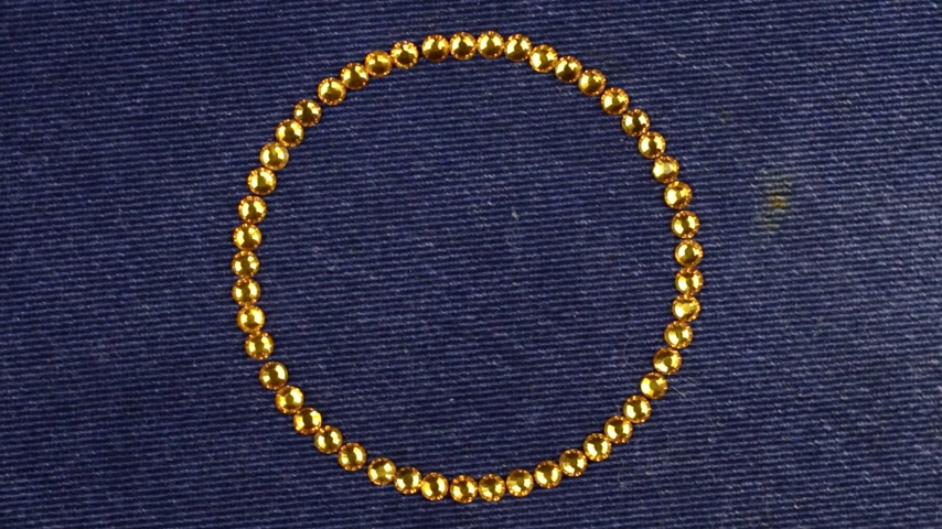 concêntrico : Rotation of a circle made of yellow rhinestones, the symbol of infinity. Top view.