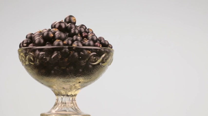 смородина : Rotation of a glass vase with a heap of black currants.