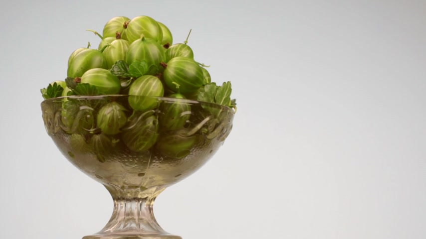 agrest : Rotation of a glass vase with a heap of green gooseberries.