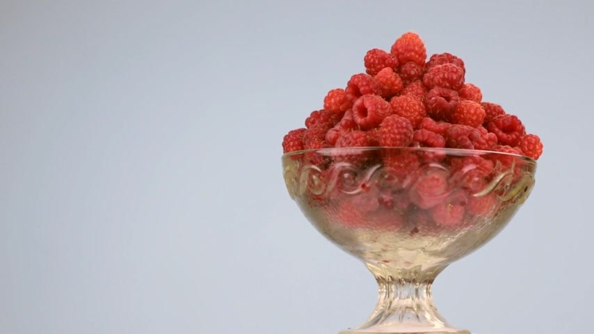 sobremesa : Rotation of a glass vase with a heap of red raspberries. Stock Footage