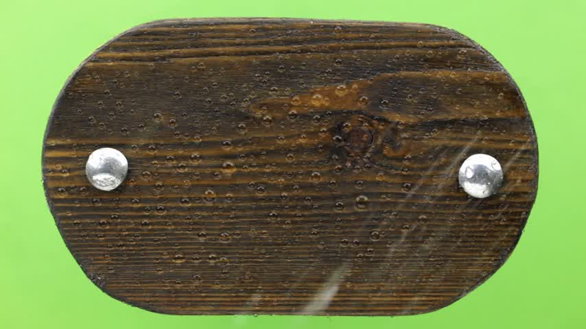 szegecs : Top view. Drops of water falling on a wooden board with iron bolts. Isolated