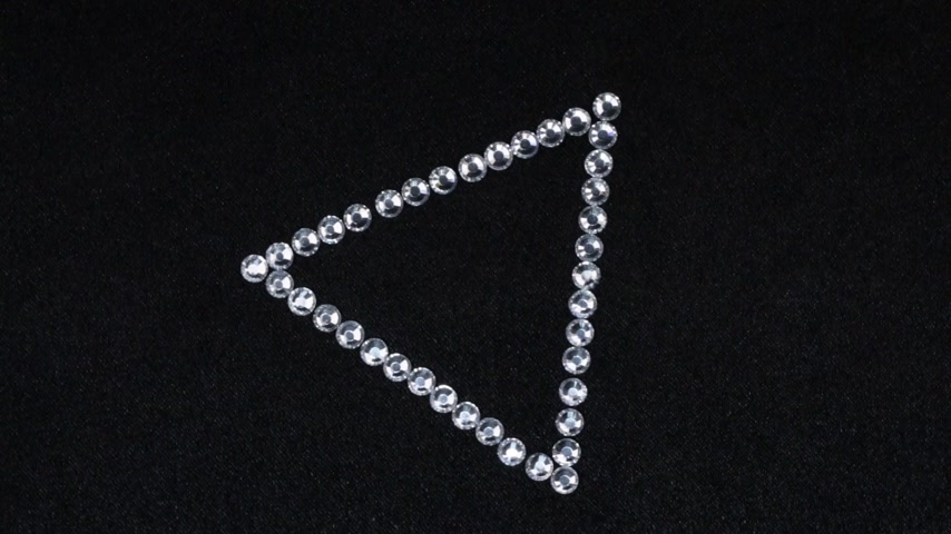 kiegészítés : Rotation of a triangle made of silver rhinestones on black fabric, the triangle symbolizes completion.