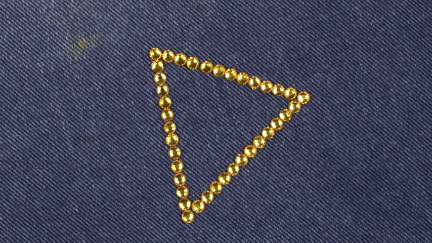 kiegészítés : Rotation of a triangle made of yellow rhinestones on denim, the triangle symbolizes completion.