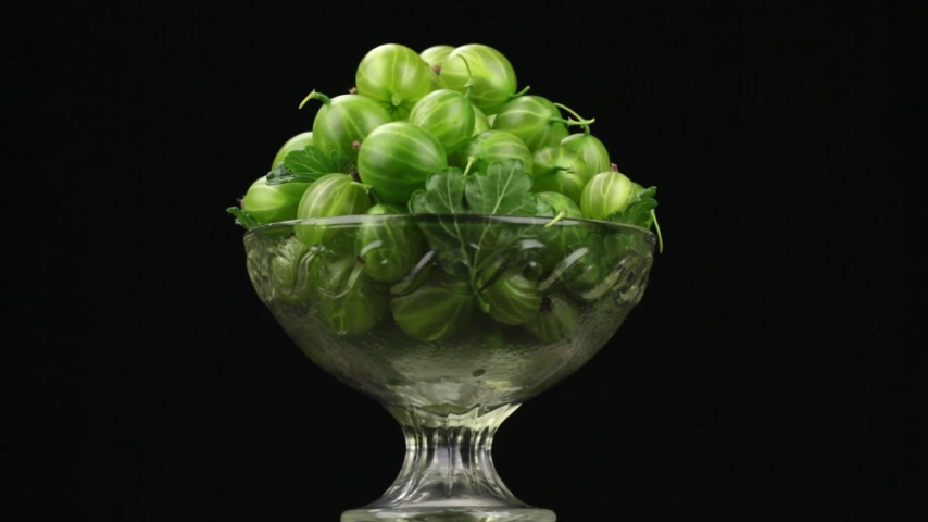 agrest : Rotation of a heap of green gooseberry lying in a glass vase. Wideo