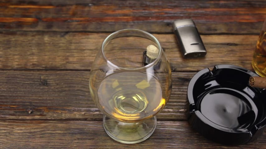 none : Slider shot. A cigar in an ashtray and a glass of alcohol are on the old table. Stock Footage