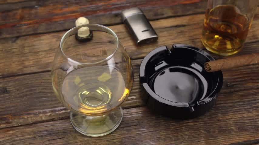 bung : Slider shot. A cigar in an ashtray and a glass of alcohol are on the old table. Stock Footage