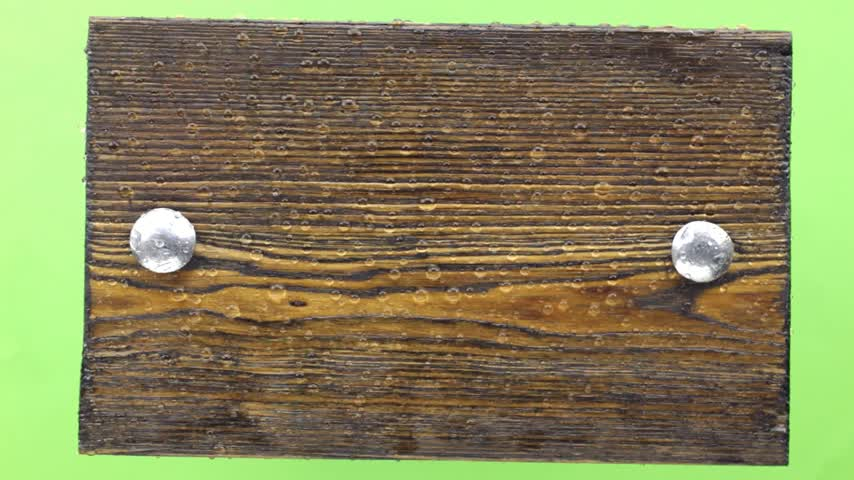 harmatcsepp : Drops of water fall on a dark wooden board with iron bolts. Isolated