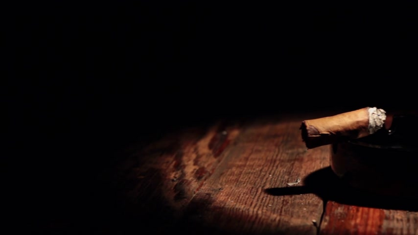 nikotin : Panorama of a cigar lying in a black ashtray in the beam of light. Stock mozgókép