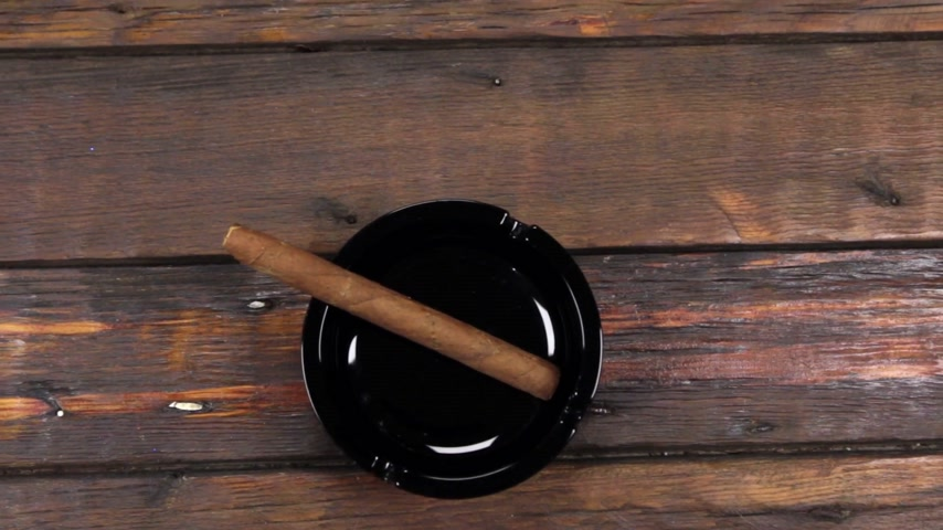 tobacco : Crane camera , moving up, cigar lies in ashtray lying on a beautiful, old wooden desk with copy space. Stock Footage