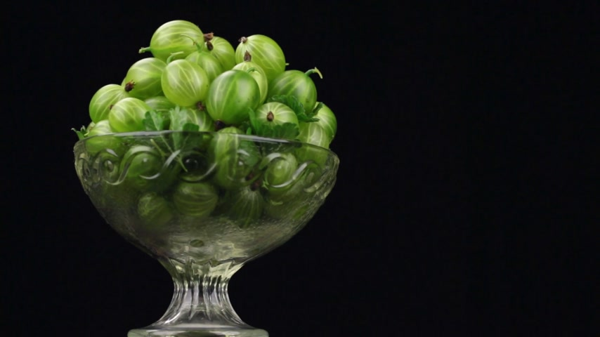 agrest : Rotation of a heap of green gooseberries in a glass vase