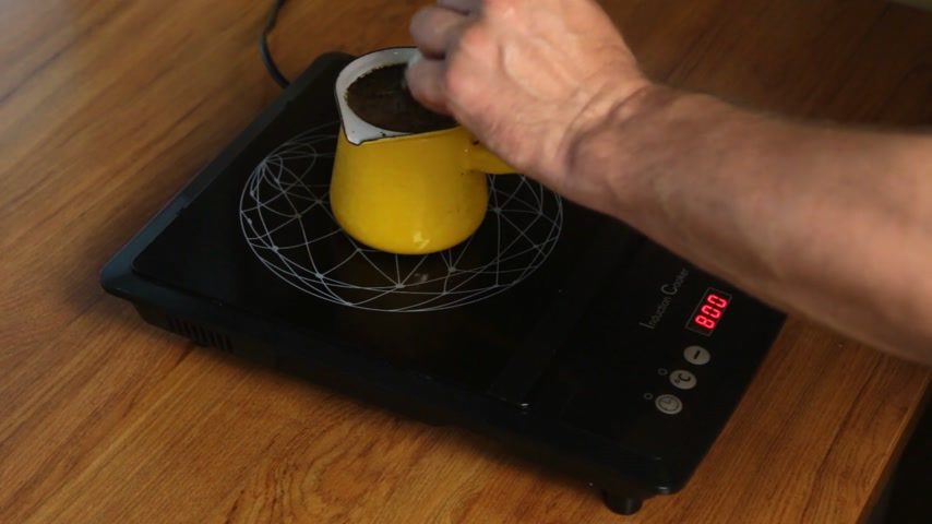 kaynatmak : Person makes coffee by adjusting the power of the induction stove.