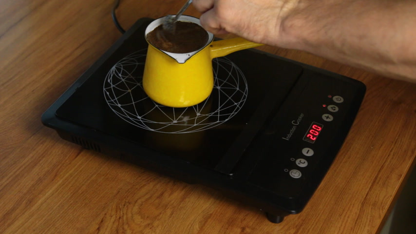 induction cooker : Person makes coffee by adjusting the power of the induction stove.