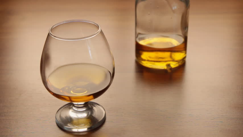 cognac : Pour cognac from bottle into glass on table Stock Footage