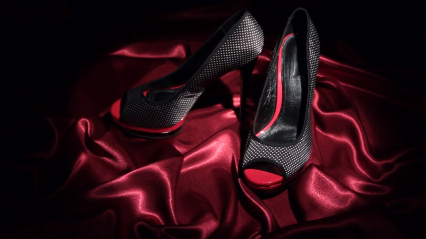 тапки : Approaching, pair of black high-heeled shoes, standing on a red cloth.