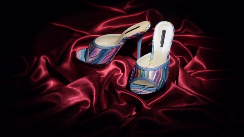 тапочка : Approaching, pair of blue clogs with high heels standing on a red cloth.