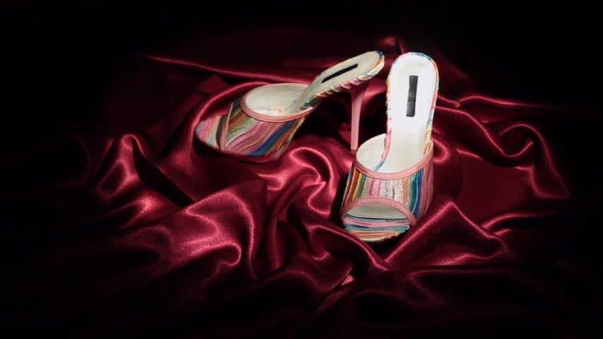sandalo : Approaching, pair of pink clogs with high heels standing on a red cloth. Filmati Stock