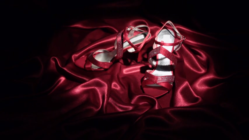тапочка : Approaching, pair of pair of red high-heeled sandals standing on a red cloth.