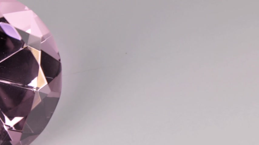 kuvars : Close-up, panorama of a large pink rhinestone on a white background. Beautiful light reflection Stok Video