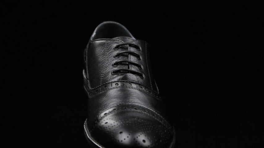 cadarço : Rotation and approximation of black classic mens shoes on a black background. Copy space.