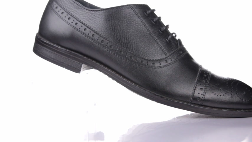 cadarço : Rotation of a stylish classic black shoe with laces on a white background.
