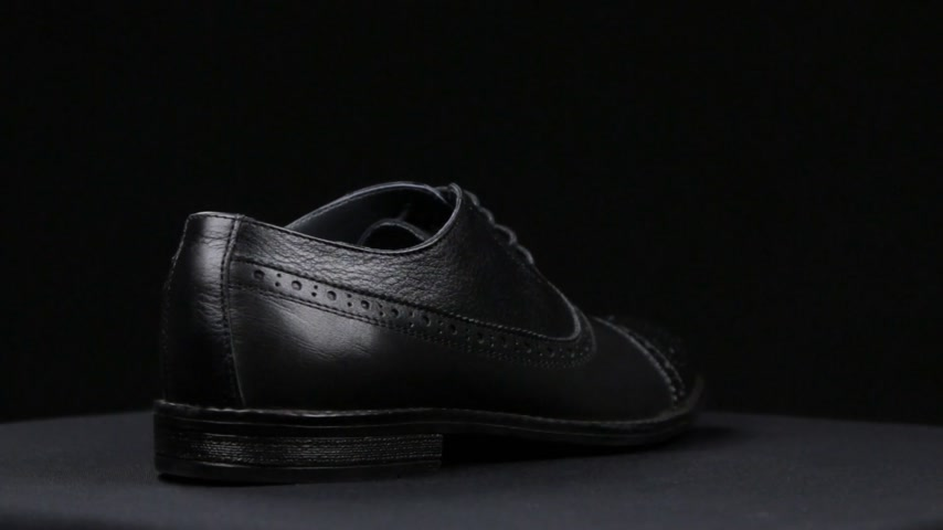cadarço : Rotation of a stylish classic black shoe with laces on a black background.