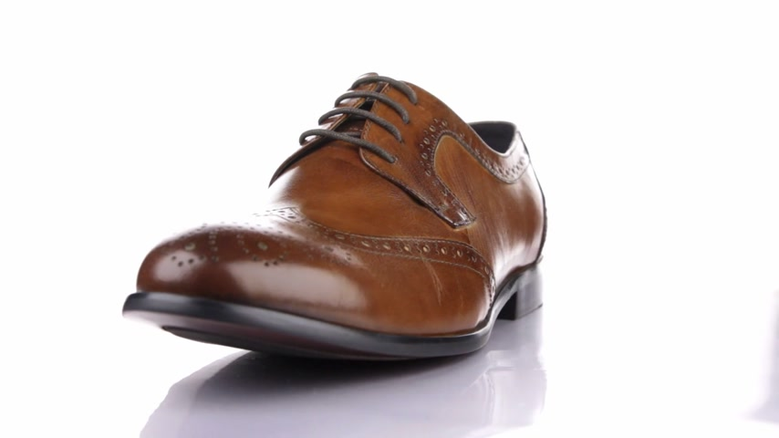 cipőfűző : Rotation of a stylish classic brown shoe with laces on a white background.