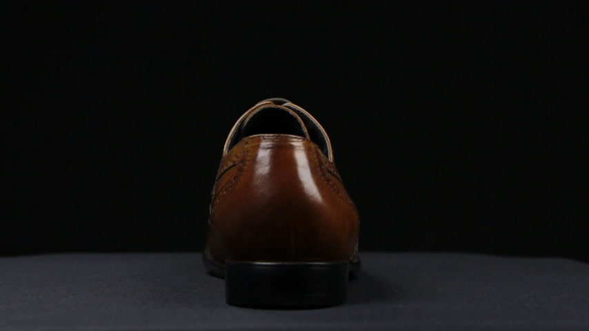 cadarço : Rotation of a stylish classic brown shoe with laces on a black background.