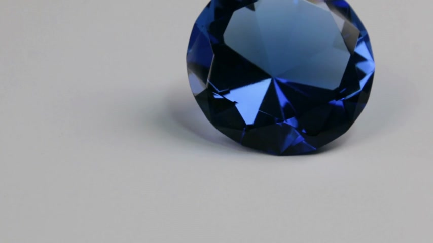 slider shot : Slider shot, large blue rhinestone on a white background. Beautiful light reflection. Stock Footage