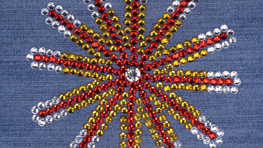 threadbare : Rotation of multi-colored rhinestones laid out in the shape of a star on denim. Stock Footage