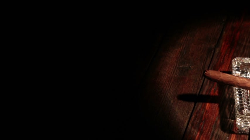cubano : Cigar lying in an ashtray on an old wooden table in a ray of light. Panorama. Vídeos