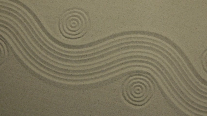 Unusual sand texture. Drawn waves and circles in the sand. With space.
