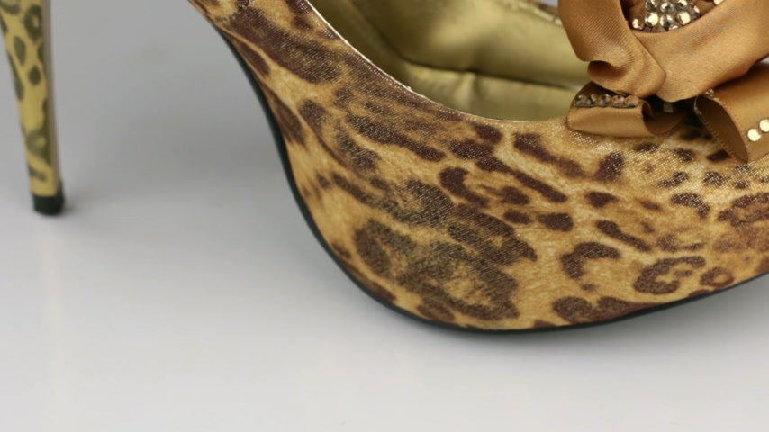 Macro, close-up. Slow rotation of leopard womens shoes on a white background.