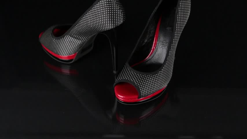 přezka : Approaching, a pair of black shoes standing on a black background. Fashion background