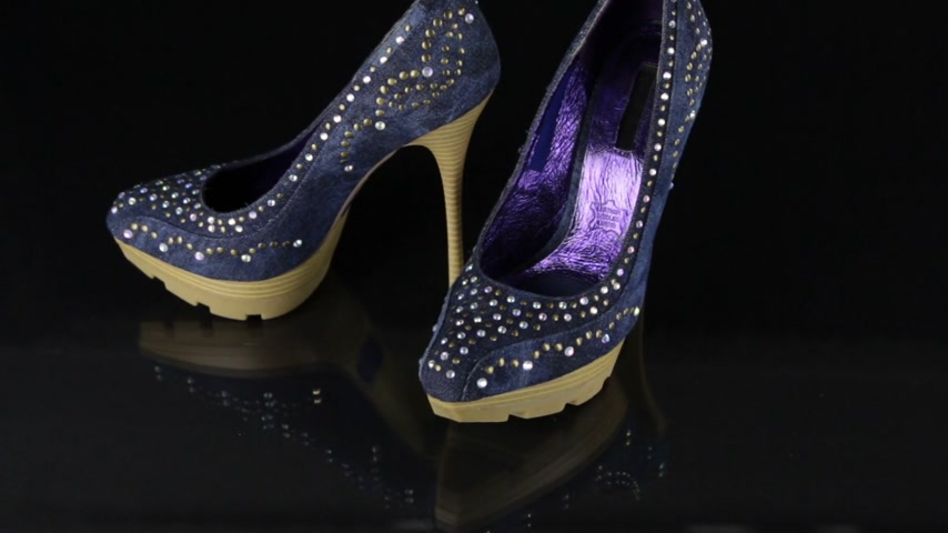 Approaching, a pair of jeans shoes with rhinestones standing on a black background. Fashion background.