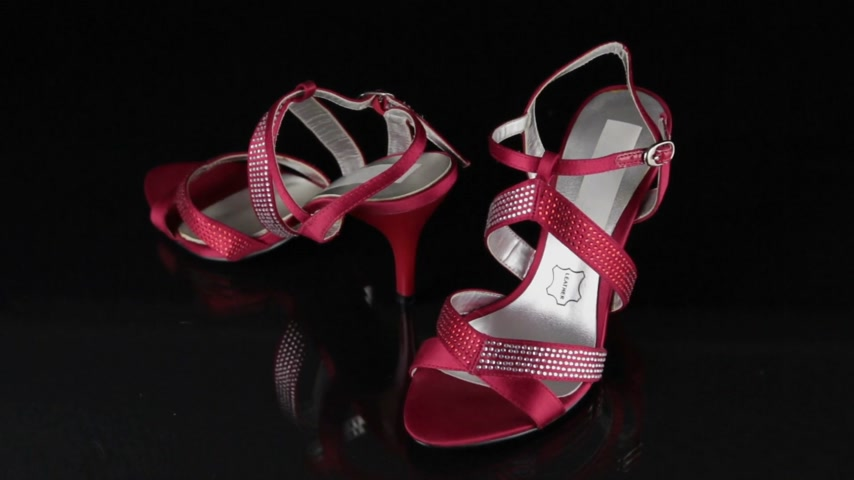 Approaching, a pair of red sandals standing on a black background. Fashion background.