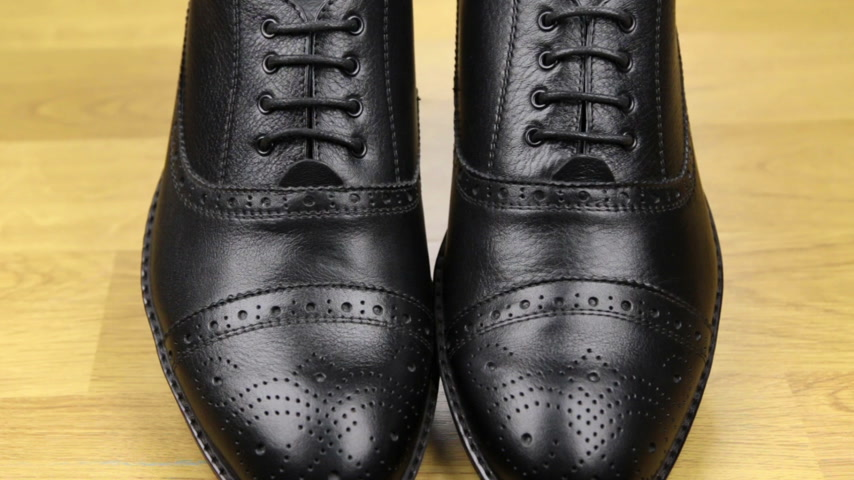 cadarço : Approaching, pair of black classic mens shoes standing on a wooden floor. Mens fashion. Vídeos