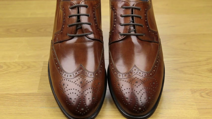 dois objetos : Approaching, pair of brown classic mens shoes standing on a wooden floor. Mens fashion.