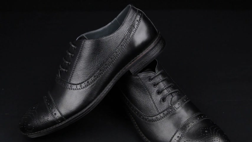 cipőfűző : Approaching, pair of black classic mens shoes standing on on a black background. Mens fashion Stock mozgókép