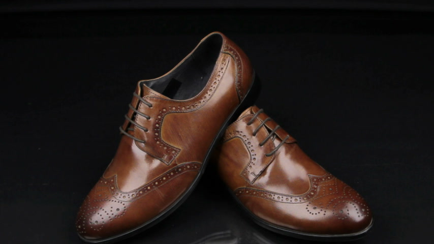 koronka : Approaching, pair of brown classic mens shoes standing on on a black background. Mens fashion