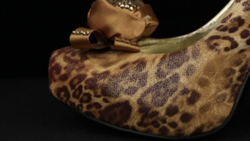 Close-up. Panorama from toe to heel of leopard womens high-heeled shoes.