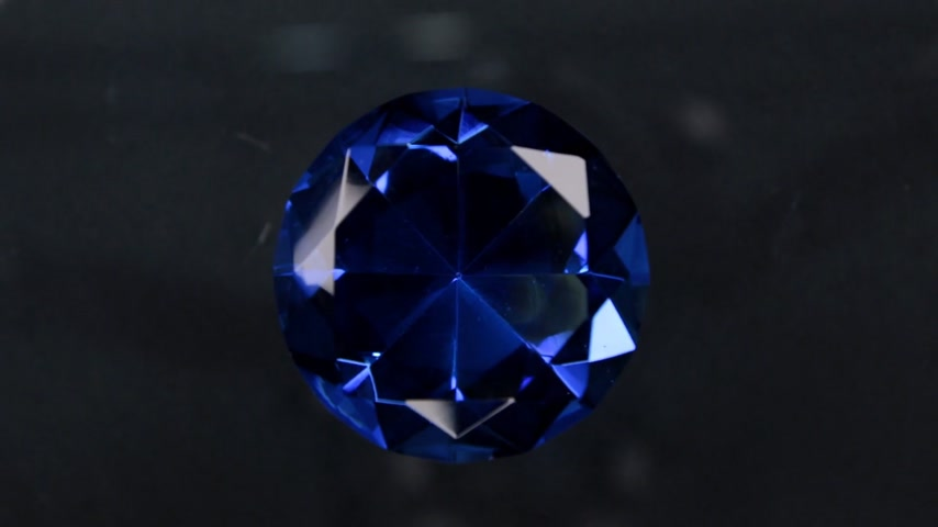 drahokamy : Rotation of a large blue rhinestone on a black background. With space for design, text place.