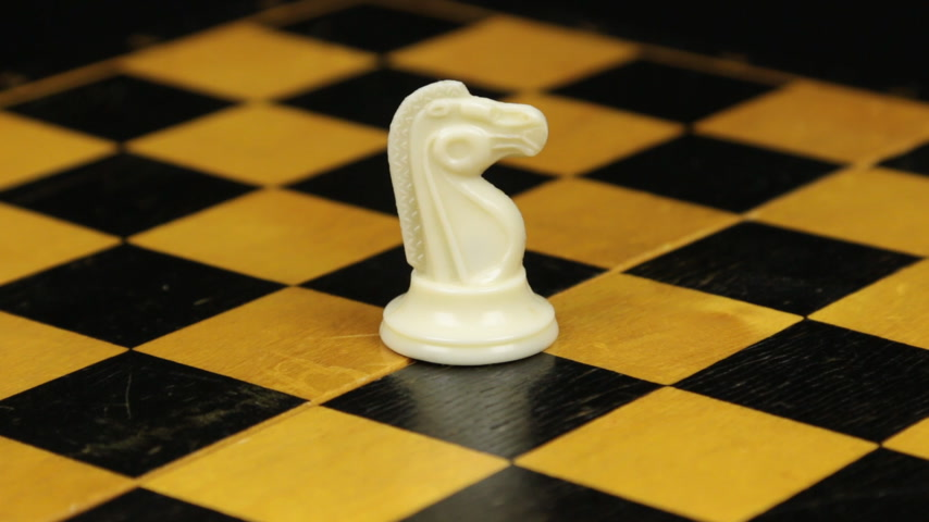 Rotation. Chess figure white horse on chess board. Close-up