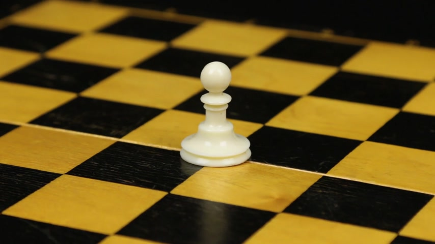 Rotation. Chess figure white pawn on chess board. Close-up