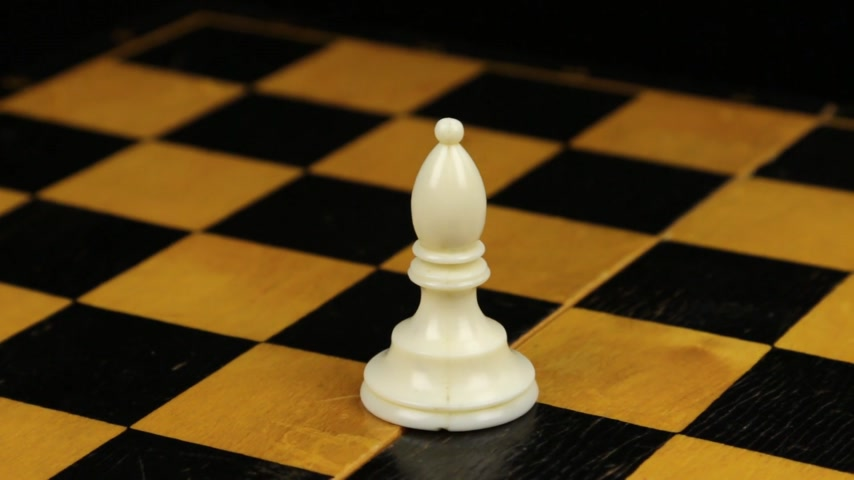 piskopos : Rotation. Chess figure white bishop on chess board. Close-up