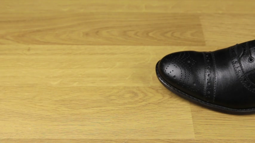 cadarço : Elegant mens shoes with laces stand on a wooden floor. The slider shot.