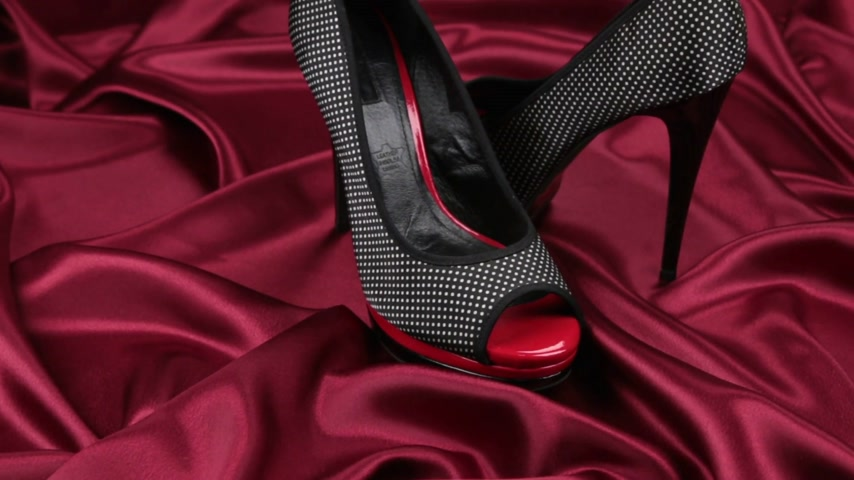 Pair of black female shoes on red cloth. Slider shot. Stock Footage