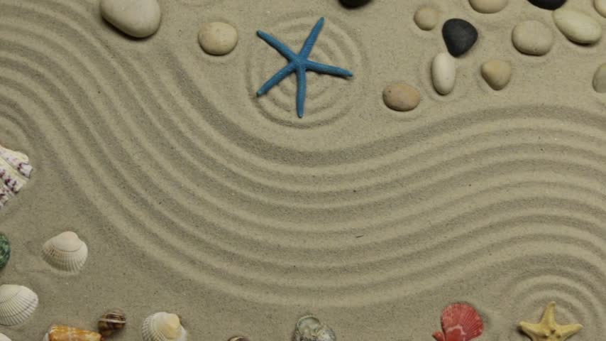 Summer background - shells, stars and stones on zigzag sand. Crane shot. Stok Video